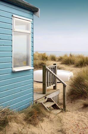 case colorate: Vista del lato di una capanna blu spiaggia in legno con terrazza in legno, guardando verso la costaspiaggia. Una barca capovolta bianca riposa davanti al rifugio tra i cespugli di sabbia e canneti. Archivio Fotografico