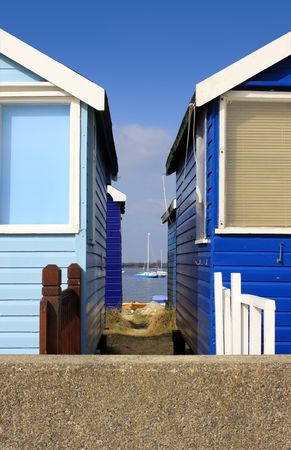 View looking through the gap between two blue wooden beach huts located in Christchurch Hampshire UK. Stock Photo - 6620157