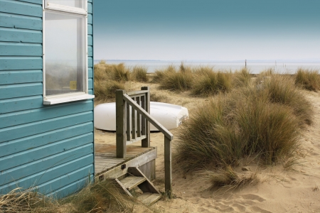 A view of a blue painted wooden beach hut with wooden terrace, looking towards the beach. An upturned white boat to front of beach hut amongst sand dunes. Set on a landscape format.