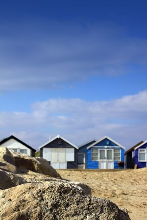 A portrait format image of blue painted wooden beach huts in soft focus to background, with sharp focus to a rock formation to front of image. Room for copy above image. Stock Photo - 6620095