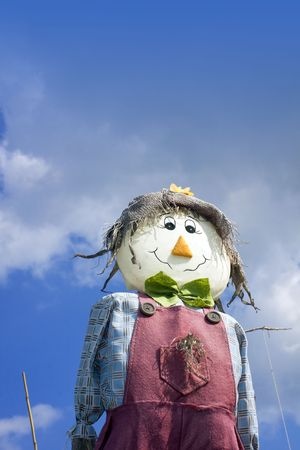 A smiling hand made scarecow stuffed with straw and wearing a red pair of dungarees with a blue checkered shirt , a green felt bow tie and a hesian hat. Set at a low angle against a blue sky background.