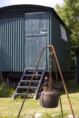 A metal cauldron hanging over an open fire space within a rusty metal frame and hook, set in front of a green painted tin constructed shepherds hut. Located in rural Dorset, England.