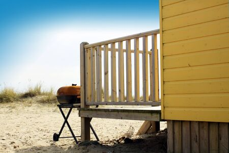 cabane plage: A yellow painted wooden beach hut with wooden decking, facing towards the sea. A BBQ sits to the front of the wooden decking. grassy sand dunes to front of beach hut. Banque d'images
