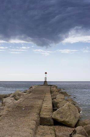 groyne: A portrait format image of a groyne marker with a view across the horizon with impending storm cloudes above. Located in Christchurch, Dorset, England.