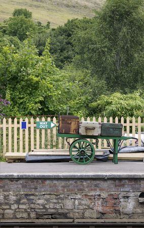 A view across a vintage railway platform looking at an old trolly with period luggage against a wooden fence. Location at Corfe Castle railway station, part of the Swanage steam railway network in Dorset, England. Stock Photo
