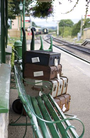 trolly: A set of period luggage with labels, consisiting of old leather cases, set on a trolly on the platform of a retro railway station. Location at Harmans Cross station on the Swanage steam railway network in Dorset. Stock Photo