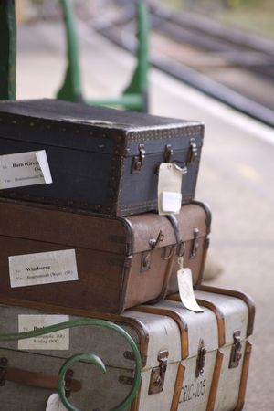 A set of period luggage consisiting of old leather cases, set on a trolly on the platform of a retro railway station. Location at Harmans Cross station on the Swanage steam railway network in Dorset. Stock Photo