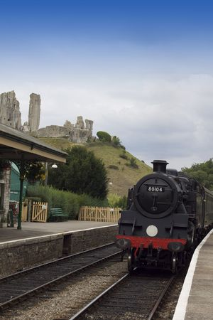 A steam train arriving at Corfe Castle Railway Station, on the Swanage railway service. Located in Dorset, Hampshire. The ruins of Corfe Castle visible in the background.