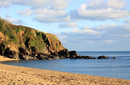 A winter beach scene. Late afternoon sunset over the cove at Blackpool Sands beach, Devon.