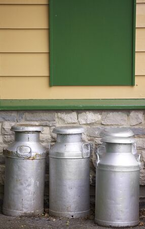 Four old tin and alluminium milk churns set in front of a wooden clad building. Located in an old railway platform in Devon, England. Part of the historical Swanage Railway system. photo