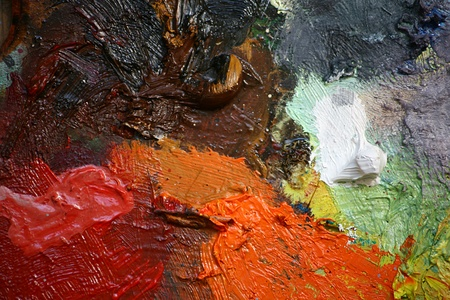 Close up detail of an artists pallet with oil paints creating an abstract pattern background, set on a landscape format.