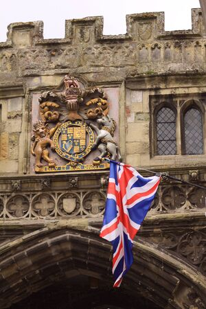 A union jack flag set against a royal crest  Crest adorns the entrance to Salisbury Cathedral - the cathedral gate  Stock Photo - 13921378