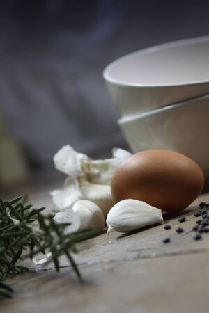 comprising: Close up detail of some kitchen ingredients comprising of a brown egg, garlic, fresh rosemary and black lentils. All set on a portrait format against a wooden background. Copy-space available.