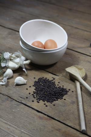 comprising: Kitchen ingredients comprising of brown eggs in a white bowl, garlic, fresh rosemary and black lentils. All set on a portrait format against a wooden background with two wooden spoons.