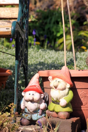 Stock Photo   Two Garden Gnomes In A City Garden Set Next To A Green  Wrought Iron And Wooden Garden Bench And In Front Of A Teracotta Coloured  Plastic Plant ...