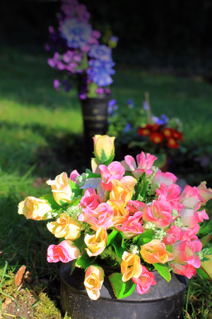 An arrangement of artificial silk roses found in a graveyard setting  Set on a portrait format  Stock Photo
