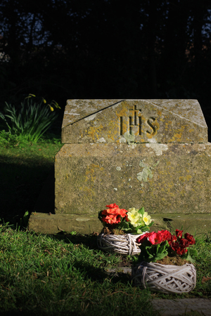 A basket of pink and yellow flowers, pansies, set in front of a weathered gravestone carved with the initials IHS  Set on a portrait format
