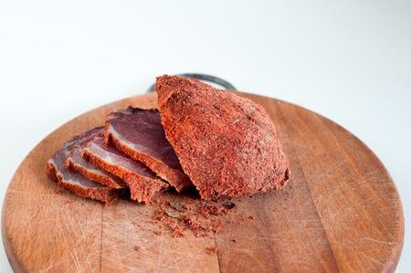 Dried beef. Sliced beef jerky. Meat on a wooden board.