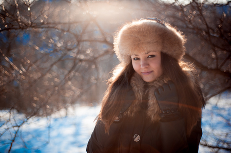 girl in warm hat with ear flaps on the background of snow-covere