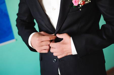 dettagli del matrimonio - il costume da smoking elegante dello sposo vestito da sposo sta aspettando la sposa Archivio Fotografico