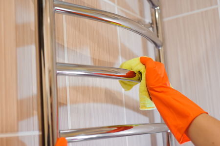 A woman washer is cleaning tiled surface in bathroom. Standard-Bild - 121931329
