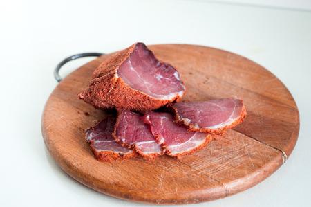 Jerky slices. Spicy Beef Jerky on vintage wooden background. Reklamní fotografie