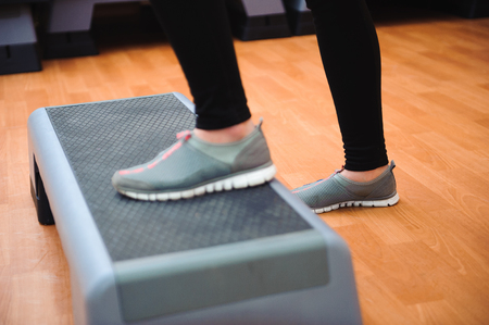 Athletic woman trainer doing aerobic class with steppers. Sport and health concept. 写真素材
