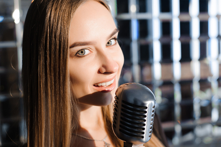 Beautiful Singing Girl. Beauty Woman with Microphone.
