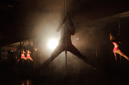 Young woman exercise pole dance on a dark background.