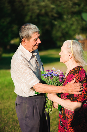 An elderly man of 80 years old gives flowers to his wife