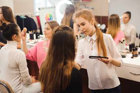 Three professional make-up artists work with beautiful women