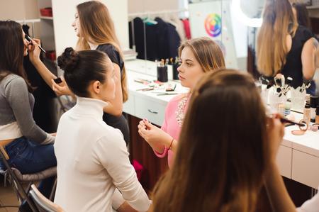 Drei professionelle Visagisten arbeiten mit schönen Frauen