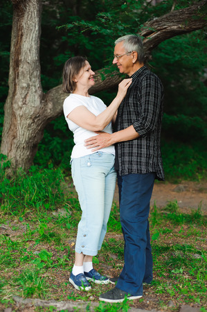 Active loving senior couple walking in beautiful summer forest
