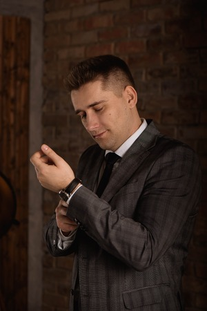Elegant businessman correcting his cufflinks and sleeve. Stock Photo