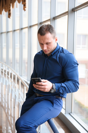 businessman looking through the phone by the window Imagens