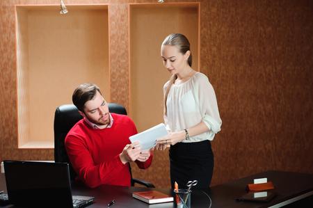Confident boss with paper explaining something to secretary Archivio Fotografico