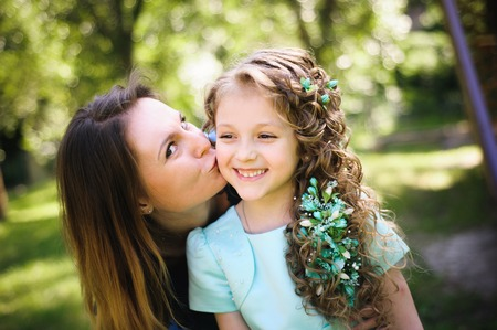 Happy mother and daughter together outdoors in a park