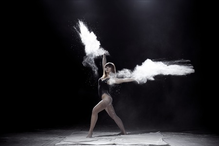 Girl dancing with a flour on black background. Zdjęcie Seryjne