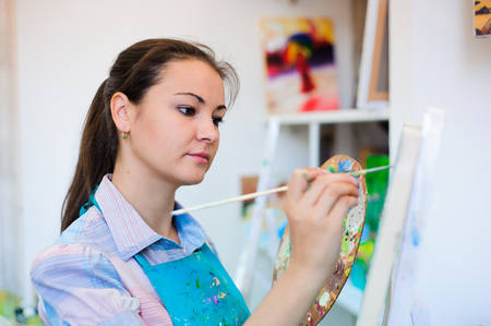 beautiful young girl draws a picture paints on art lesson. Stock Photo