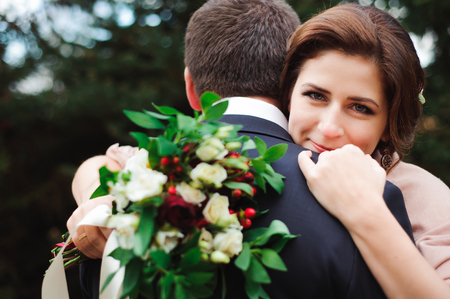 Romantic embrace of newlyweds. Couple walks in the park Фото со стока
