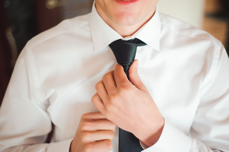 Young businessman puts a suit on before meeting with partners.