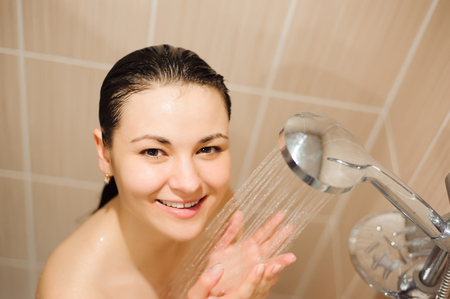 beautiful young woman smiling while taking shower