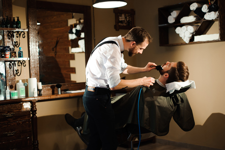 Master cuts hair and beard of men in the barbershop