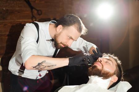 Meister schneidet Männerhaare und Bart im Barbershop