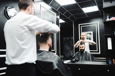 Young handsome barber making haircut of attractive man in barbershop. 免版税图像