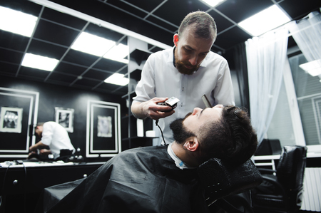 Master cuts hair and beard of men in the barbershop, hairdresser makes hairstyle for a young man. 스톡 콘텐츠