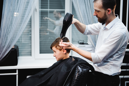 Cute little boy is getting haircut by hairdresser at the barbershop Banco de Imagens