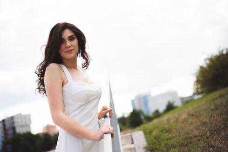 piękna młoda dziewczyna w białej sukni na schodach