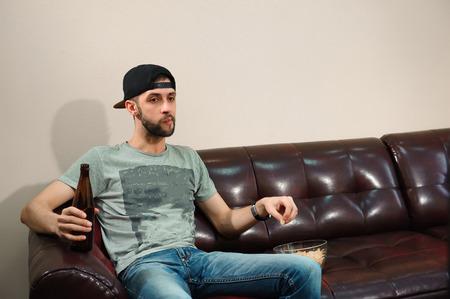 Hombre viendo fútbol, bebiendo cerveza, aficionado al fútbol Foto de archivo