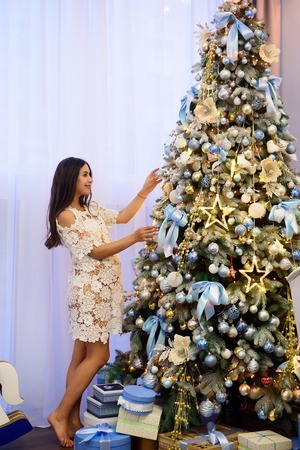 Beautiful pregnant young woman decorates a Christmas tree